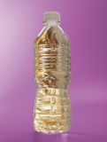 Gold Water bottle on magenta Royalty Free Stock Image