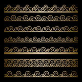 Gold wavy borders. Set of wavy gold borders, ornamental lines on black Royalty Free Stock Photo