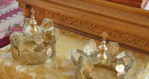 Gold wedding crowns of marriage in a church, move camera close up.  stock video footage