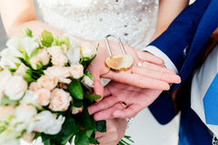 Gold wedding lock in the form of heart in the hands. Of the bride and groom Stock Images