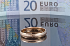 Gold wedding ring on the background of Euro banknotes Royalty Free Stock Photos