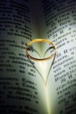 Gold wedding Ring on a bible. A wedding ring makes a heart shaped silhouette in  open  Bible Royalty Free Stock Photography