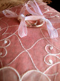 Gold wedding rings. Two wedding rings on pink broidered cushion Stock Images