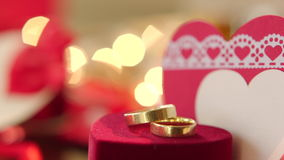 Gold wedding rings with bokeh lights. And valentine on the background stock video