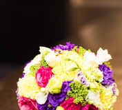 Gold wedding rings on a bouquet of colourful flowers Stock Images