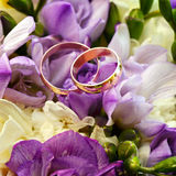 Gold wedding rings on a bouquet of flowers Royalty Free Stock Photos
