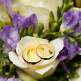 Gold wedding rings on a bouquet of flowers for  bride Royalty Free Stock Images