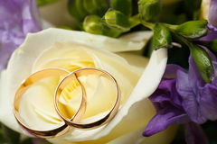 Gold wedding rings on a bouquet of flowers Stock Photos