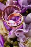 Gold wedding rings on a bouquet of flowers Stock Photography