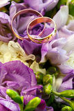 Gold wedding rings on a bouquet of flowers Royalty Free Stock Photo