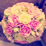 Gold wedding rings on a bouquet of pink flowers. Square format, toning instagram stock image