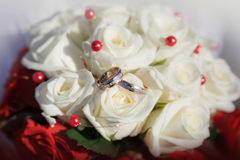 Gold wedding rings on a bouquet of roses Royalty Free Stock Photos