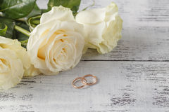 Gold wedding rings on a bouquet of white roses Stock Images