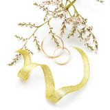 Gold wedding rings and branch flowers Royalty Free Stock Image