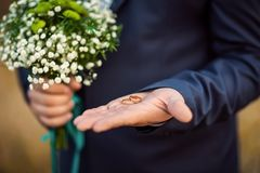 Gold wedding rings in the bride`s hand in a suit with a bouquet of flowers of white color.  Stock Photo