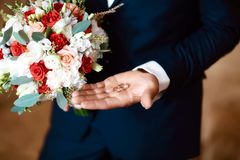 Gold wedding rings in the bride`s hand in a suit with a bouquet of flowers of white and red color.  Royalty Free Stock Photos