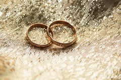 Gold wedding rings. On a gold cloth background Royalty Free Stock Photo