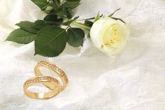 Gold wedding rings with diamonds and rose on white Stock Photo