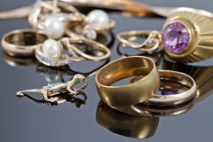 Gold wedding rings, earrings and chains Royalty Free Stock Photography