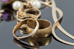 Gold wedding rings, earrings and chains Stock Photography