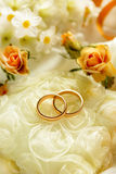 Gold wedding rings with flowers around. Closeup Stock Photography