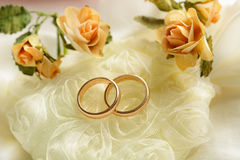 Gold wedding rings with flowers around. Closeup Royalty Free Stock Photography
