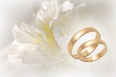 Gold wedding rings on flowery festive background. Two gold wedding rings on flowery festive background royalty free stock image