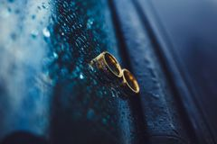 Gold wedding rings. On the car window Royalty Free Stock Photo
