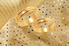 Gold wedding rings on golden festive background Stock Image