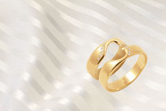 Gold wedding rings on golden festive background Royalty Free Stock Images