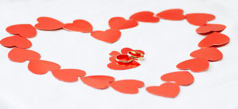 Gold wedding rings and hearts. Stock Image