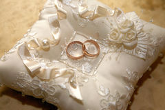 Gold wedding rings lie on a decorative pillow Stock Photo