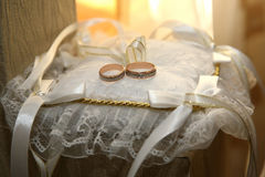 Gold wedding rings lie on a decorative pillow Royalty Free Stock Image