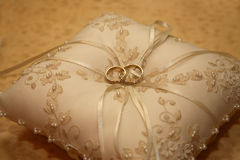 Gold wedding rings lie on a decorative pillow Royalty Free Stock Photos
