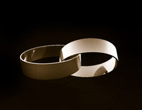 Gold wedding rings linked together Stock Image
