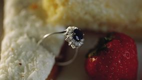 Gold wedding rings macro closeup in a cake with coconut and strawberries diamond jewellery. Jewellery macro highlight wedding rings couple symbol of happiness stock footage
