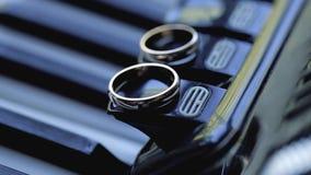 Gold wedding rings macro closeup on a musical instrument diamond jewellery. Jewellery macro highlight wedding rings couple symbol of happiness stock footage