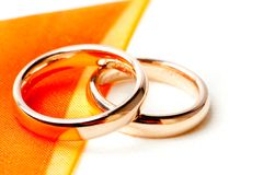 Gold wedding rings near orange ribbon Royalty Free Stock Photography