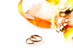 Gold wedding rings near ribbon and flowers with space for text. On white background stock illustration