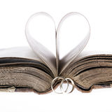 Gold wedding rings,old book and paper heart. On a white background royalty free stock photography