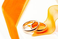 Gold wedding rings orange ribbon Stock Image