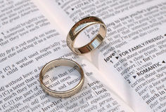 Gold wedding rings on a page showing love Stock Photo