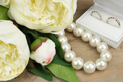 Gold Wedding Rings, Pearl necklace and Peony flowers. Close-up. Royalty Free Stock Photos