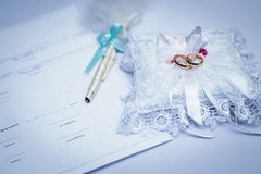 Gold wedding rings. With pen on  the table Royalty Free Stock Photos
