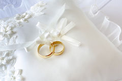 Gold wedding rings on a pillow with ribbons.  Royalty Free Stock Image