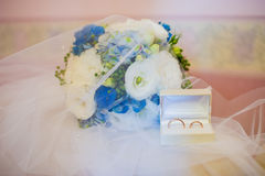 Gold wedding rings on the pincushion and beautiful blue and whit Stock Photography