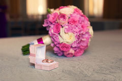 Gold wedding rings and pink bridal bouquet Royalty Free Stock Images