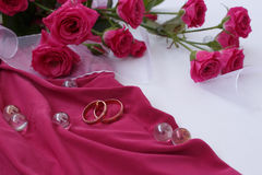 Gold wedding rings on pink fabric with white ribbon and roses. Gold wedding rings on fabric with white ribbon and roses Royalty Free Stock Photo