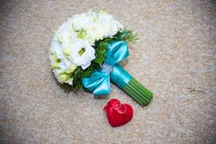 Gold wedding rings in a red box and bridal bouquet. Gold wedding rings in a red box and a bridal bouquet stock photography