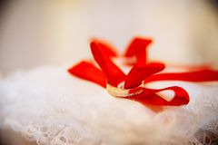 gold wedding rings on red stock image